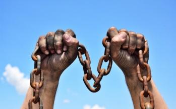 dos-manos-masculinas-sosteniendo-cadena-metal-oxidado_116441-3926